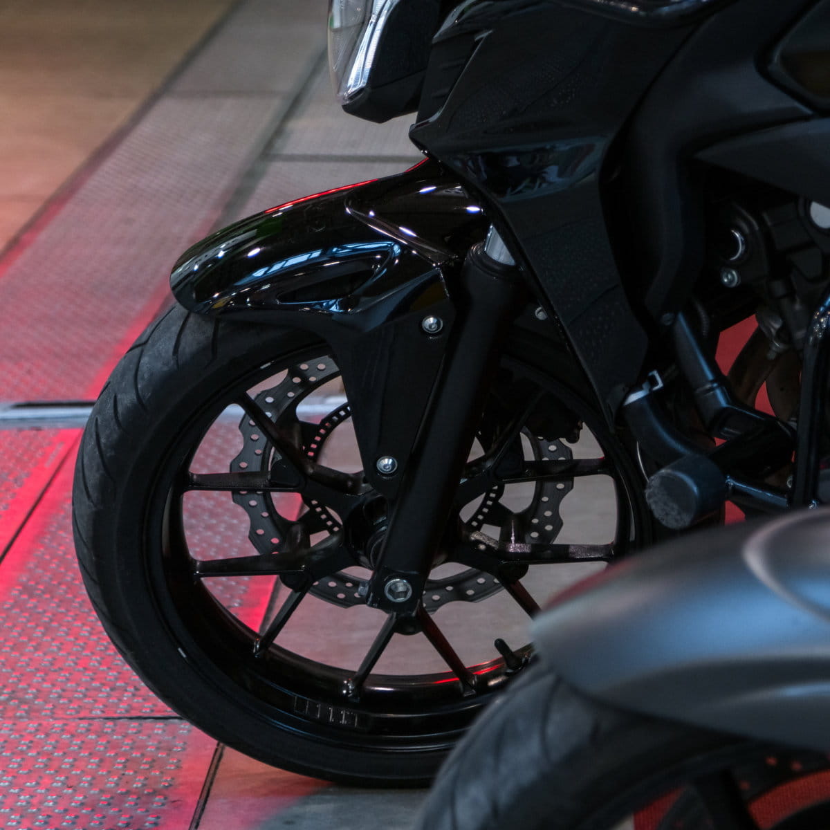 Front wheel of modern black motorcycle on concrete and metal ground