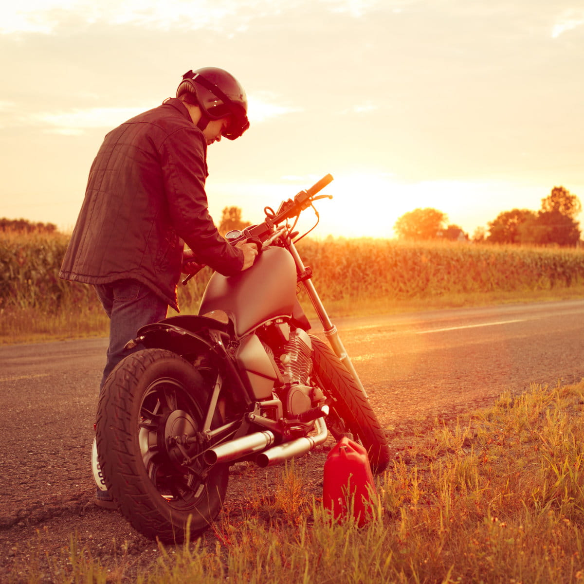 Man next to a motorcycle out of gas
