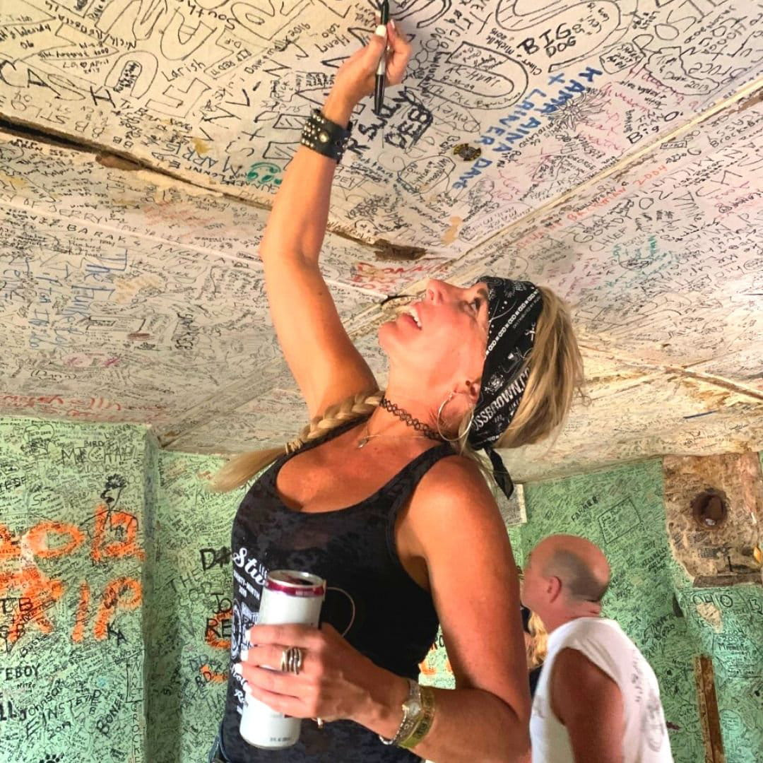 biker chick signing her name on the ceiling in a bar