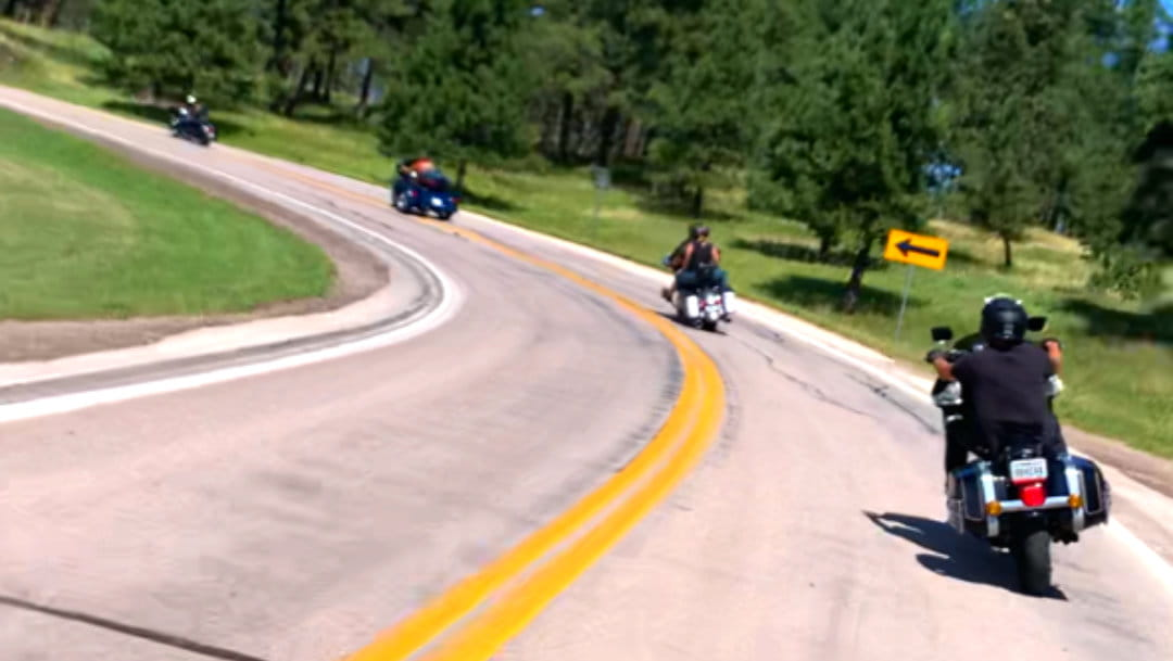 four bikes riding around a curve on a sunny day