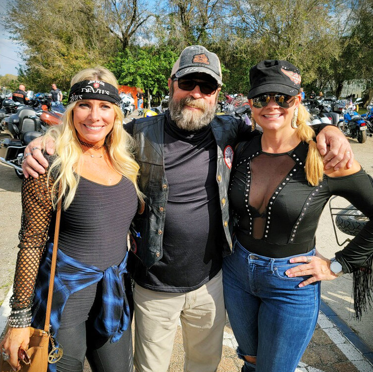 Two women and a man at a biker event posing for a picture