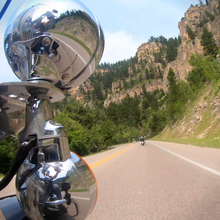 Motorcycle taking a curve around Spearfish Canyon