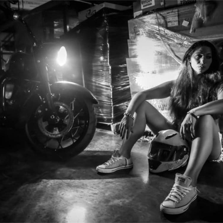 Young girl sitting on the floor in a warehouse next to a motorcycle with its headlight on